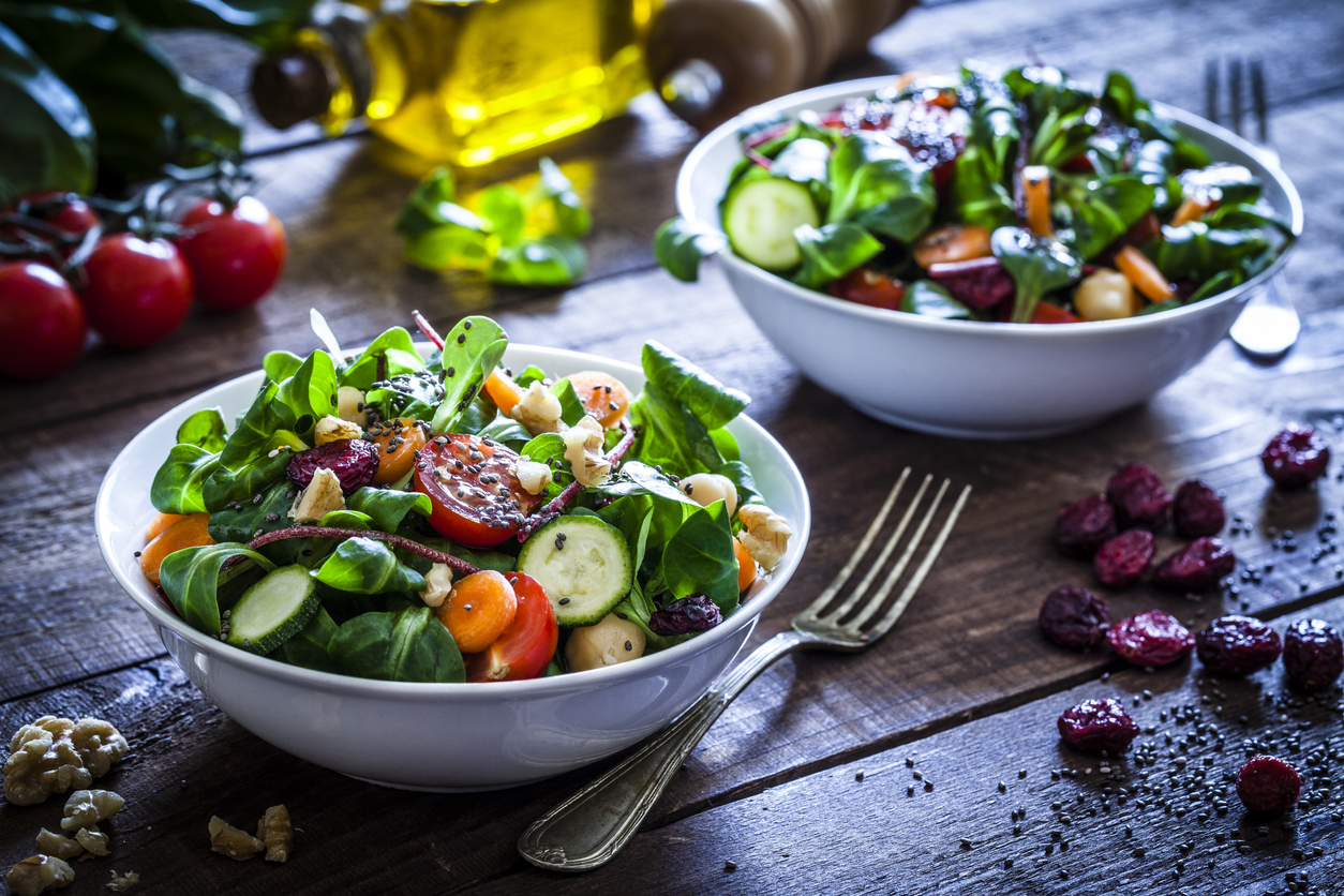two bowls of salad sitting on wooden table