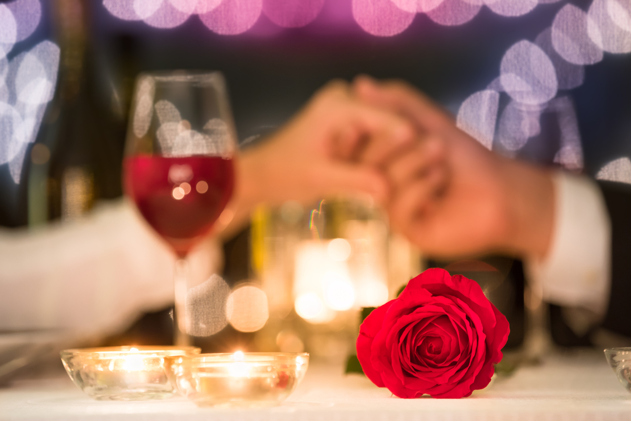 couple-holding-hands-at-romantic-dinner-date-with