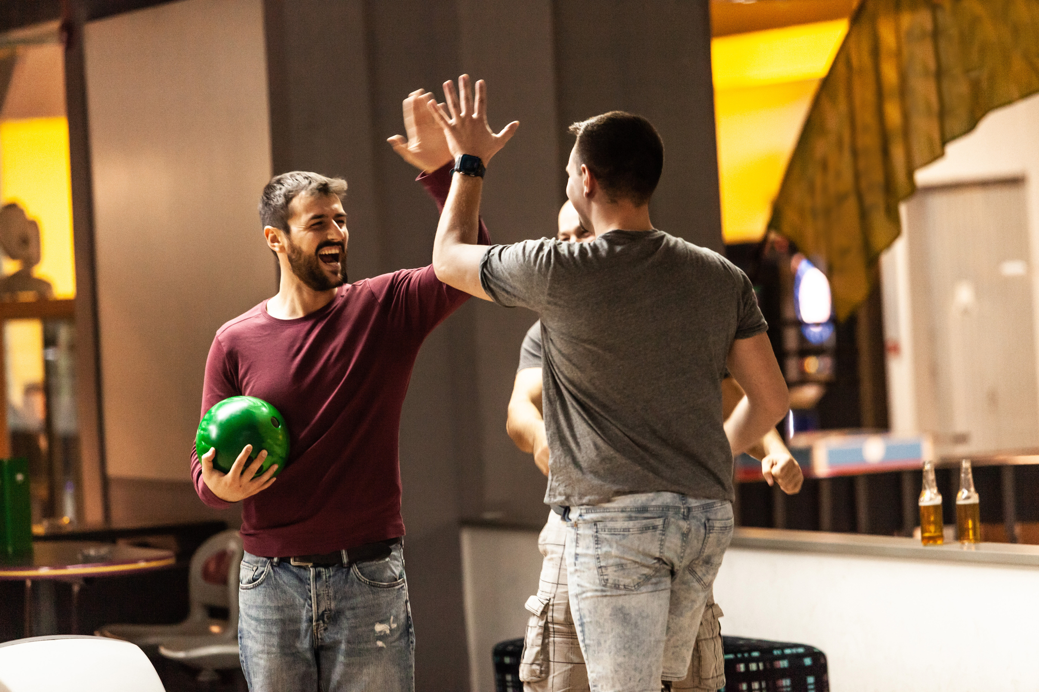 Three men are high fiving and celebrating their score in bowling. indoor activities in lone tree