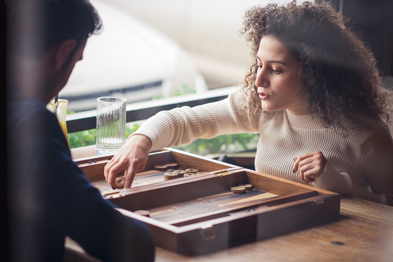 Two people playing backgammon at home