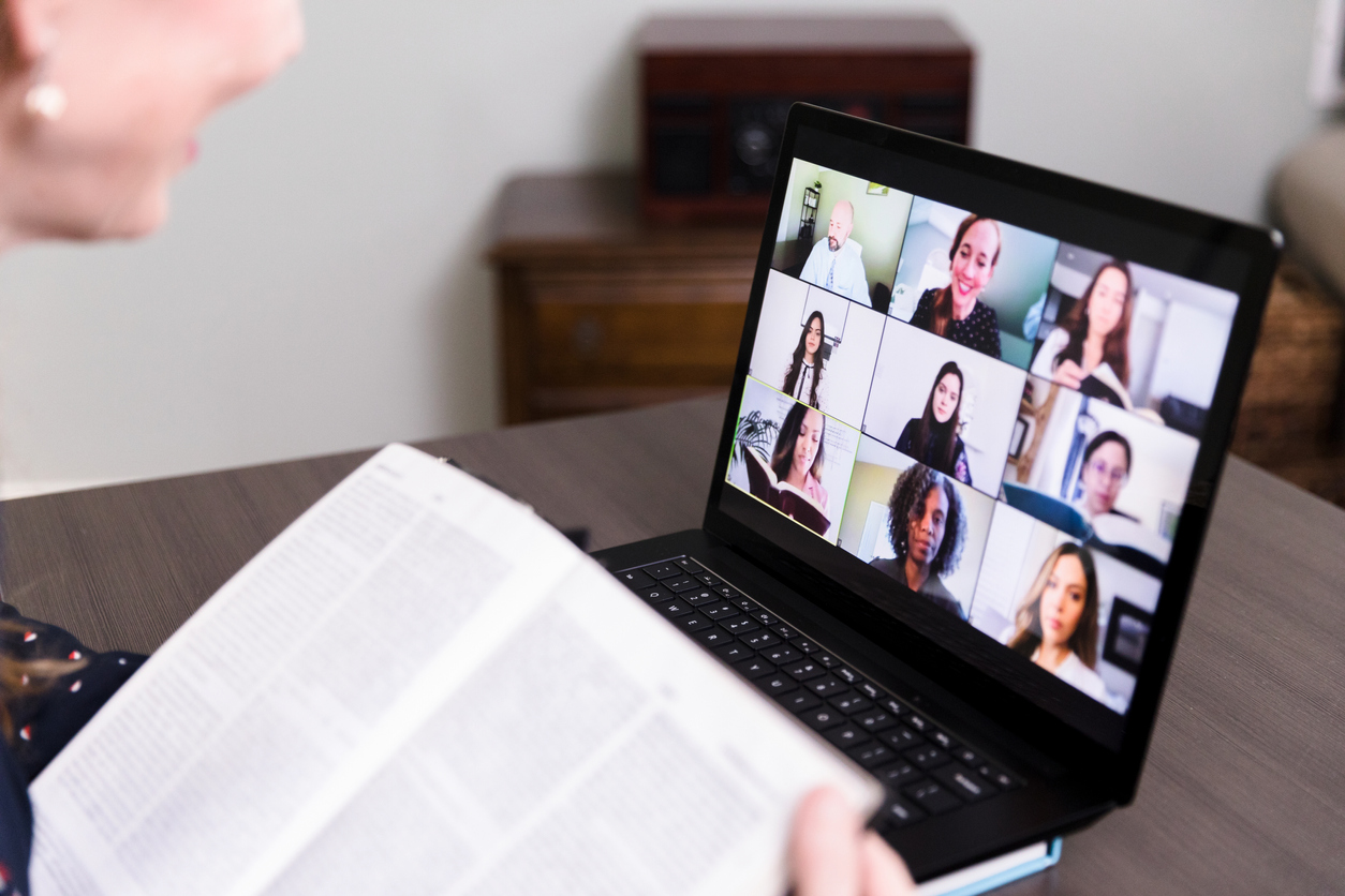 A woman uses her laptop at home to video conference with her friends for their monthly book club: apartments in Lone Tree