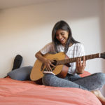 woman playing a guitar in her room | virtual music classes around Lone Tree