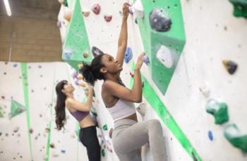 two friends climbing an indoor wall | indoor rock climbing near Lone Tree